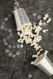 Palomitas en las tazas grises de papel de la Navidad blanca para las reuniones de las vacaciones de invierno con los amigos con l Fotos de archivo