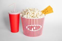 Palomitas sabrosas, taza con la bebida y boletos de la película imagen de archivo