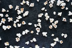 Palomitas saladas blancas dispersadas en la tabla de madera fotografía de archivo