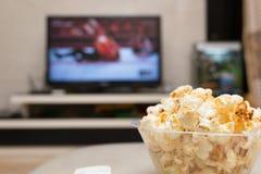 Palomitas y teledirigido en el sofá con una difusión de TV que lucha fotografía de archivo