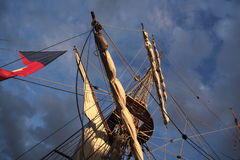Palos altos y aparejo de la nave silueteados contra un cielo dramático en la puesta del sol Imagenes de archivo