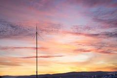 Palos de las telecomunicaciones de las antenas de televisión contra una puesta del sol fotografía de archivo