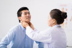 Palpating lymph node. Female doctor palpating lymph node of a young man Stock Photo