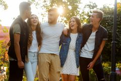 Pals having fun together. Stylish young people walking, chatting and laughing. Funny and carefree time royalty free stock image