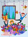 palying与圣诞节庆祝背景的礼物的孩子 免版税库存图片
