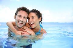 palying在游泳池的夫妇 库存图片