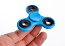 Palying with a blue Fidget Spinner. Royalty Free Stock Image