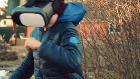 Palying kämpfendes Spiel des kleinen Jungen unter Verwendung des Kopfhörers der virtuellen Realität im Hinterhof stock footage