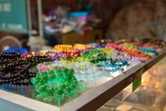 Pamiątkarscy szklani koraliki różni kolory kłamają na kontuarze Pojęcie uliczny handel błyskotki, tanie imitacje obraz royalty free