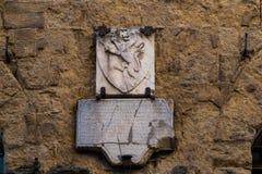 Pamiątkowy kamień z dalej nakrywa nieokiełznanego lwa w San Gimignano zdjęcia royalty free