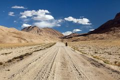 Pamir highway Pamirskij trakt with biker, there is one of the best cycling road on the world. Unpaved road in Tajikistan, roof. Pamir highway or Pamirskij trakt stock images
