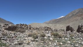 Pamir Highway Ratm Fort. Ruins Wakhan Corridor View with Snow Capped Mountains at Background on a Sunny Blue Sky Day stock footage