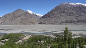 Pamir Highway Wakhan Corridor. Landscape View from Abrashim Qala Fortress in Zong of the Snow Capped Mountains of Afghanistan on a Sunny Blue Sky Day stock video footage