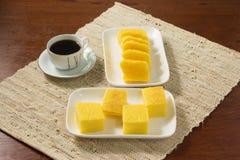 Pamonha y Canjica/Curau en una placa blanca con una taza de café en taza del wtithe En un fondo rústico imagenes de archivo