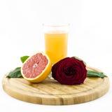 Pampelmuse - Frucht und Saft auf hölzernem Brett mit rosafarbener Blume Stockbilder