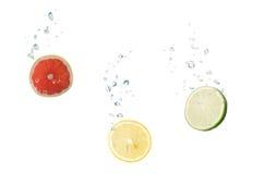 Pampelmuse, Zitrone, Kalk im Wasser mit Luftblasen stockfoto
