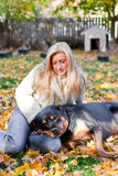 Pampered pets. Woman and her dog laying on golden maple leaves outside on a cold autumn afternoon Stock Photos