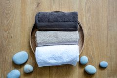 Pampering ręczniki i zen kamienie na round naturalnym drewnianym tle obrazy royalty free