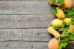 Pampkin e zucchini con le foglie verdi sulla tavola di legno d'annata Fondo del raccolto di autunno Immagine Stock Libera da Diritti