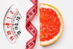 Pamplemousse avec la bande de mesure sur l'échelle de poids dieting images stock