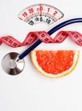 Pamplemousse avec la bande de mesure sur l'échelle de poids dieting images libres de droits