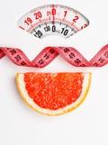 Pamplemousse avec la bande de mesure sur l'échelle de poids dieting photos libres de droits