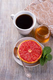 Pamplemousse cuit au four avec du miel et une tasse de café noir Images stock