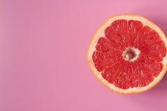 Pamplemousse d'agrume sur un fond rose dans une coupe photo stock