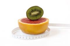 Pamplemousse et kiwi rouge, coupe dans la moitié et ruban métrique Photos libres de droits