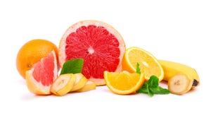 Pamplemousse rouge frais avec les tranches jaunes de citron et de banane, menthe parfumée d'isolement sur un fond blanc photographie stock libre de droits