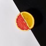Pamplemousses et moitiés oranges d'agrumes Images stock