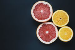 Pamplemousses et oranges sur le fond noir La tranche porte des fruits papier peint Rouge, jaune, fruits frais Image libre de droits