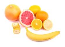 Pamplemousses lumineux, citrons, oranges, tranches de bananes et banane entière, fruits sains pour la santé d'isolement sur un bl Photos libres de droits