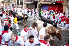 PAMPLONA, SPAIN -JULY 8: Unidentified men run from bulls in street Estafeta during San Fermin festival in Pamplona, Spain on July stock photo