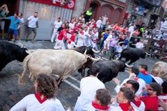 PAMPLONA, SPAIN -JULY 8: Unidentified men run from bulls in stre. Et Estafeta during San Fermin festival in Pamplona, Spain on July 8, 2013 Royalty Free Stock Image