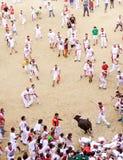 PAMPLONA SPANIEN - JULI 9: Folk som har gyckel med unga tjurar på Royaltyfria Foton