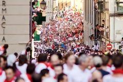 PAMPLONA SPANIEN - JULI 9: Folket kör från tjurar på gatan Santo D Arkivfoton