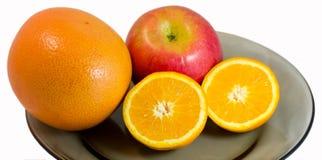 Pamplumossa, maçã e metade da laranja em uma placa Foto de Stock