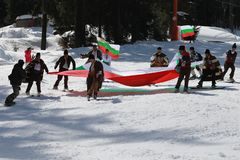 People dressed with traditional Bulgarian clothes skiing with the Bulgarian national flag. royalty free stock photo