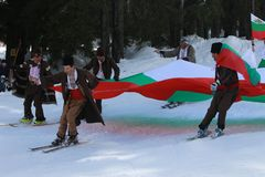 People dressed with traditional Bulgarian clothes skiing with the Bulgarian national flag. stock images