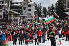 People dressed with traditional Bulgarian clothes skiing with the Bulgarian national flag. stock image