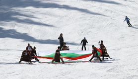 People dressed with traditional Bulgarian clothes skiing with the Bulgarian national flag. stock photography