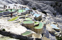 Pamukkale. Tourists on original site of Pamukkale in Turkey, done by hard water springs that create natural limestone basins full of water Stock Images