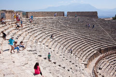 PAMUKKALE, TURKEY - September 13, 2015: Tourists regard antique amphitheater in the ancient city of Hierapolis. Pamukkale, Turkey. Royalty Free Stock Image