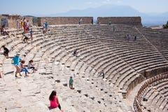 PAMUKKALE, TURKEY - September 13, 2015: Tourists regard antique amphitheater in the ancient city of Hierapolis. Pamukkale, Turkey. Royalty Free Stock Image