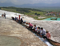 Pamukkale Turkiet - April 26, 2015: Turistfoten som fördjupas i vattenflöden som kommer från travertinen, terrasserar Arkivbild