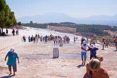 PAMUKKALE TURKIET - September 13, 2015: Turister betraktar travertinesna med tips och terrasser på Pamukkale Royaltyfri Bild