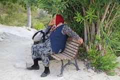 PAMUKKALE, TURQUÍA - 22 DE AGOSTO DE 2017: Asientos de una más vieja mujer en un banco, relajando y disfrutando de un día hermoso imagen de archivo