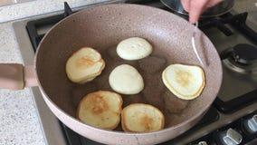 PanÑ  akes που τηγανίζει σε ένα τηγάνι που το χέρι γυναικών αναποδογυρίζει με το δίκρανο απόθεμα βίντεο