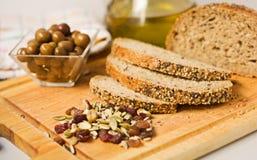 Pan, aceitunas, germen y aceite de oliva. Foto de archivo libre de regalías
